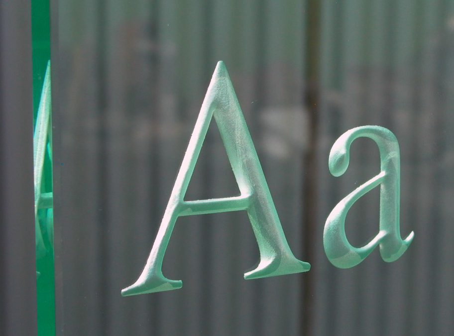 gestraalde letters in glas